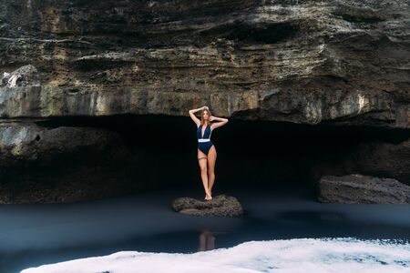 Sexy girl poses in blue swimsuit near cave on black sand beach, concept travel Foto de archivo - 127807974