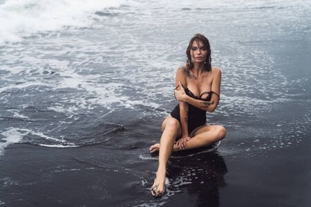 Sensual girl in swimsuit with wet hair sits on black sand beach in ocean waves Archivio Fotografico