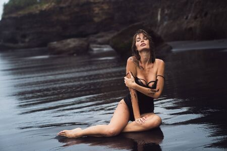 Sensual sexy girl in swimsuit with wet hair sits on black sand beach Foto de archivo