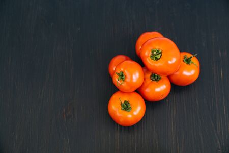 Top view of red cherry tomatoes on black wooden background with copy space
