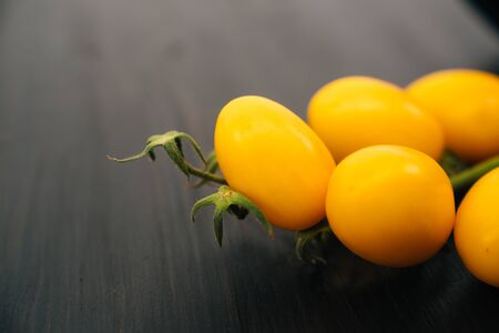 Top view of yellow cherry tomatoes on black wooden background Archivio Fotografico
