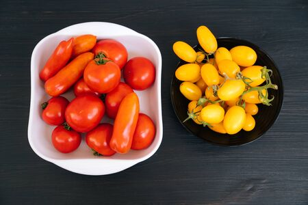 Top view of yellow, red cherry tomatoes in black, white bowl on dark background