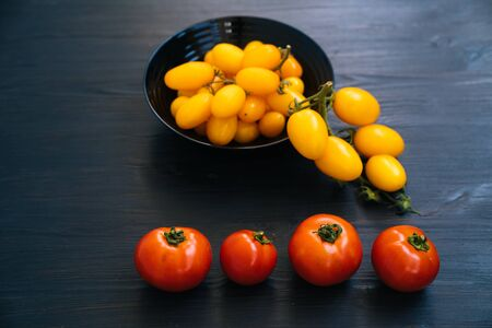 Top view of yellow and red cherry tomatoes in bowl on black wooden background