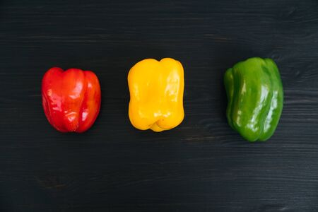 Top view of red, yellow, green bell peppers on black wooden background Foto de archivo - 132053504