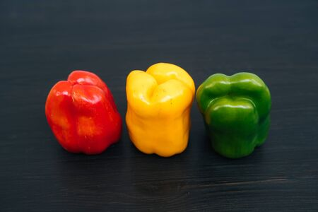 Top view of red, yellow, green bell peppers on black wooden background