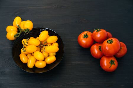 Top view of yellow and red cherry tomatoes in black bowl on wooden background Stock Photo