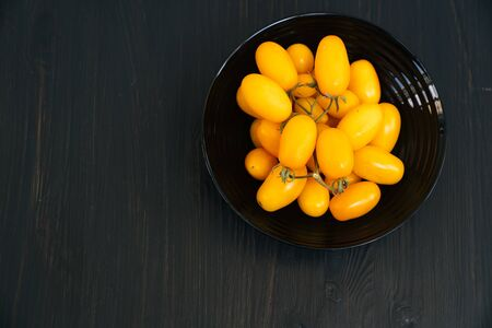 Top view, yellow cherry tomatoes in bowl on black wooden background, copy space