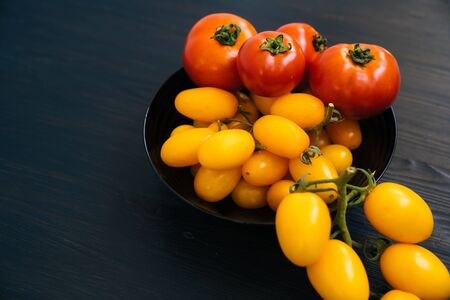 Top view of yellow and red cherry tomatoes in black bowl on wooden background Archivio Fotografico
