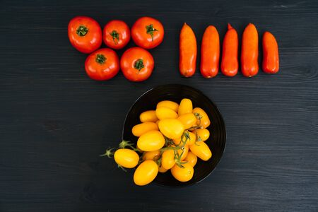 Top view of yellow and red cherry tomatoes in bowl on black wooden background with copy space. Concept of vegetable