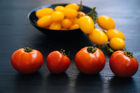 Top view of yellow and red cherry tomatoes in bowl on black wooden background. Concept of vegetable