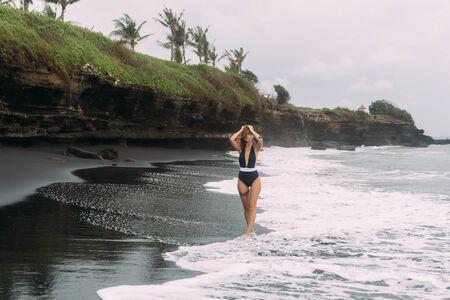 Beautiful girl in dark swimsuit walks on black sand beach near ocean