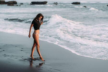 Girl with sexy body in black T-shirt and swimwear walks on black sandy beach Foto de archivo