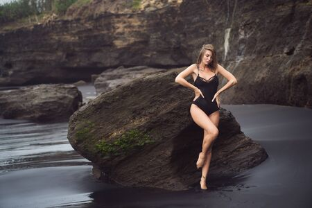 Young sexy woman in swimsuit resting on black sandy beach on vacation Foto de archivo - 132575747