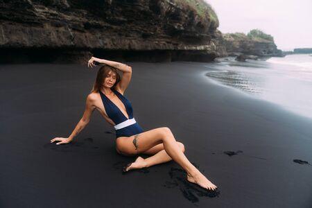 Sexy model in dark swimwear rests on black sand beach Standard-Bild