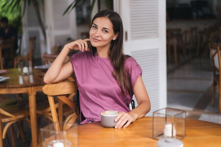 Portrait of beautiful woman drinking hot beverage from cup in cafe and smiling Foto de archivo - 146875926