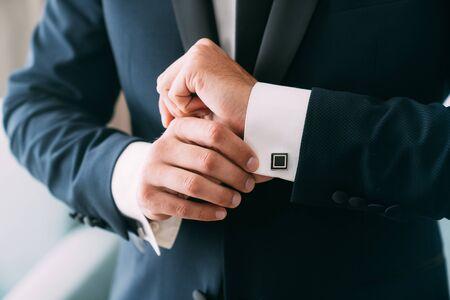 Close-up groom hands puts on cufflinks. Elegant gentleman clothes, white shirt Standard-Bild