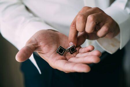 Close-up groom hands holds cufflinks. Elegant gentleman clothes, white shirt