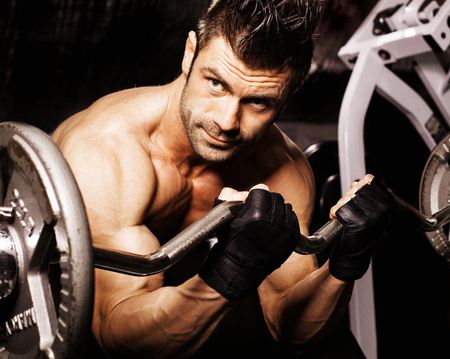 the man in the gym dumbbell raises