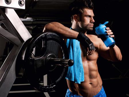 gimnasio: el hombre en el gimnasio bebiendo de la coctelera azul