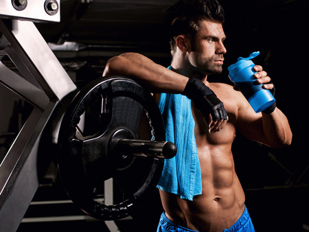 the man in the gym drinking from the blue shaker Stock Photo