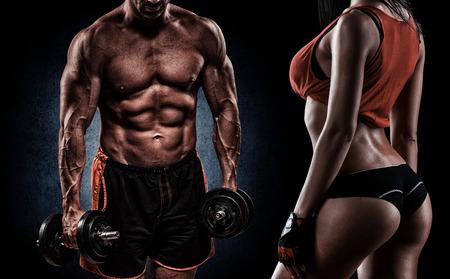fitnes: jonge knappe man doen oefening met halters in de studio op donkere achtergrond
