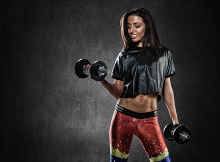 beautiful young sports girl does exercises with dumbbells