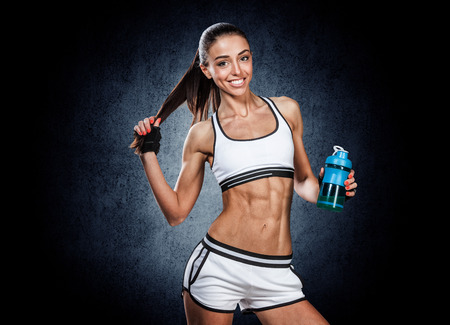 fitnes: jonge mooie sport meisje poseren met een fles in zijn hand Stockfoto
