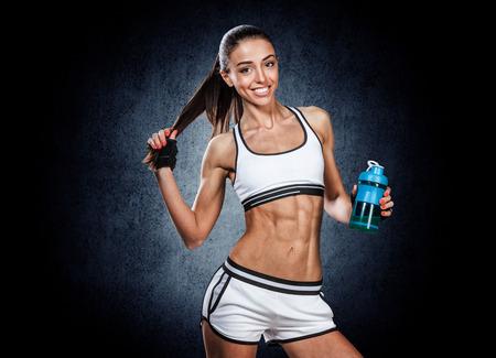 fitness: Rapariga bonita desportivo que levanta com uma garrafa na m�o