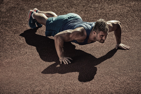 man gym: male model performs pushup on floor. Stock Photo