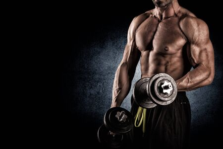naked male body: young handsome man doing exercises with dumbbells on a dark background