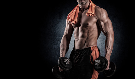 with dumbbells over black background