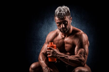 healthy living: tired after training a young man, drinking a protein from banks