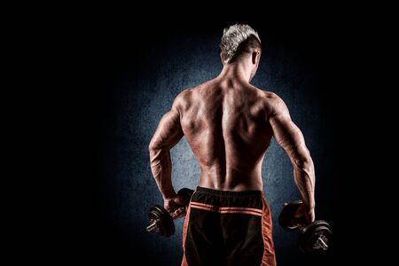 cuerpo hombre: hombre guapo joven haciendo ejercicios de espalda en un fondo oscuro