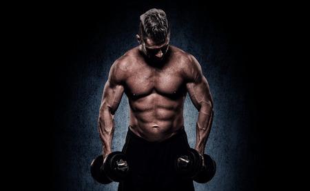 cuerpo hombre: apuesto joven sobre fondo de pared haciendo ejercicios para el bíceps