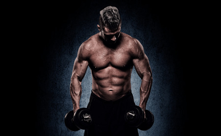 gym: handsome young man on wall background doing exercises for the biceps Stock Photo