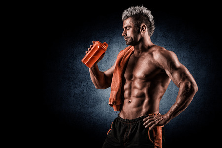 muscle: joven guapo con músculos fuertes, bebida de proteína después del entrenamiento Foto de archivo
