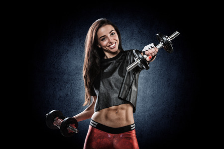 beautiful young athletic girl smiling and doing exercises with dumbbells