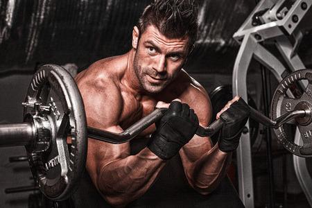 hombre fuerte: Hombre hermoso con los músculos grandes, que presenta en la cámara en el gimnasio Foto de archivo