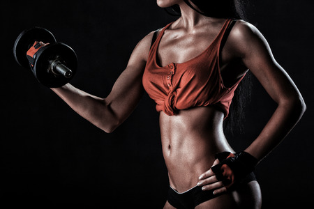 body pump: beautiful woman on a dark background is engaged in fitness Stock Photo