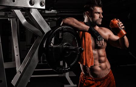 desnudo: muscular hombre joven y guapo bebe una prote�na en el gimnasio Foto de archivo