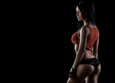 beautiful woman on a dark background is engaged in fitness 版權商用圖片
