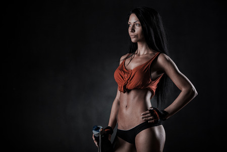 beautiful woman on a dark background is engaged in fitness Stok Fotoğraf