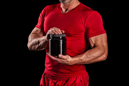 nutrition: beautiful young athletic man holding a jar of sports nutrition Stock Photo