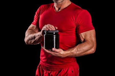 alimentacion: hermoso hombre atlético joven que sostiene un frasco de nutrición deportiva
