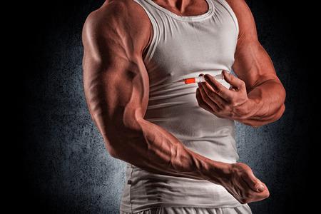 inyeccion: hombre muscular que hace un tiro en el bíceps, los esteroides, la farmacología