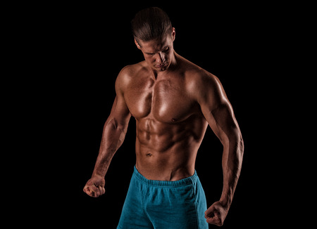 fitness gym: handsome muscular young man posing in front of the camera in the studio Stock Photo
