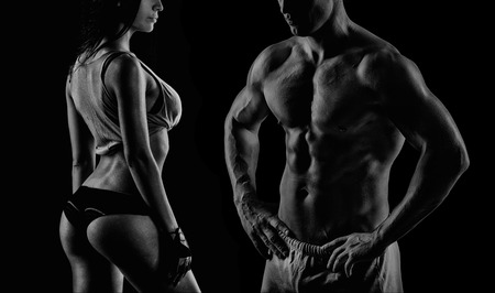 フィットネス: 女の子とカメラにポーズ スタジオで若い筋肉男