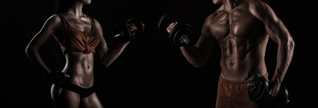 gym: handsome young muscular couple doing exercises with dumbbells
