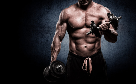 bodybuilder: apuesto joven en pantalones cortos, haciendo ejercicios de bíceps, sobre un fondo oscuro en el estudio Foto de archivo