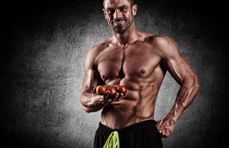 muscle training: sportlich junger Mann mit Kohl in den Händen von